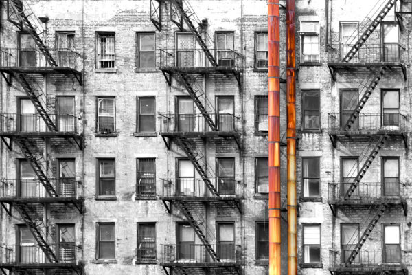 Black and white apartment building with colorful old rusted meta