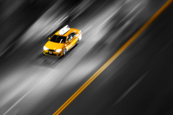 New York City yellow taxi in motion speeding down the street on