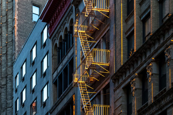 Warm glow of sunlight shining on a fire escape on the front of a