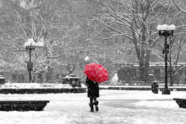 Woman with red umbrella in black and white New York City snow