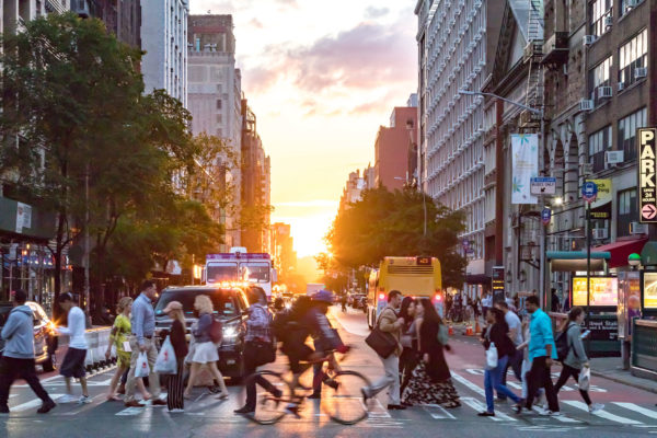 NEW YORK CITY - JUNE, 2018: Crowds of people cross a busy inters