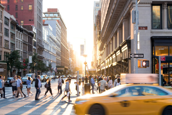 New York City yellow taxi cab speeds past the crowds of people a