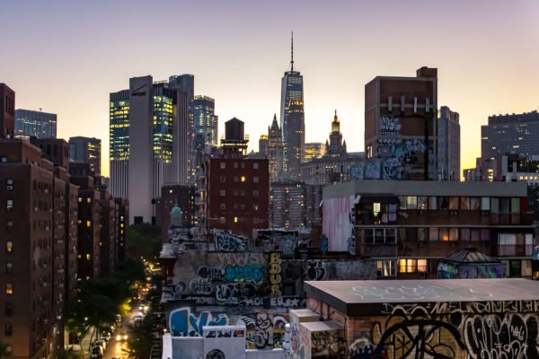 The colorful lights of the NYC skyline shine as evening falls on