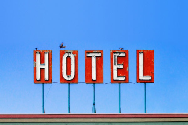 Red hotel sign on top of a dirty old motel isolated on blue sky